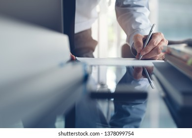 Signing contract, business deal concept. Businessman, executive manager working in modern office, make a deal, signing business contract with laptop computer, digital tablet on office desk.