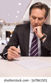 Signing a contract. Thoughtful mature man in formalwear signing a document and holding hand on chin