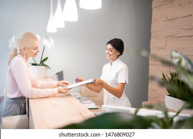 Signing papers. Cheerful administrator standing at reception desk showing the client way of filling up the form.