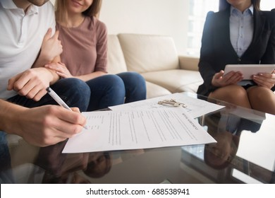 Signing rental agreement by young couple of renters or tenants, sitting on sofa with female real estate agent, male hand with a pen putting signature, long-term rent of property, close up