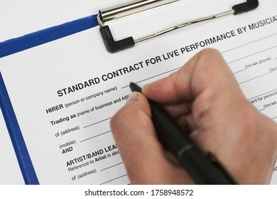 Signing standart contract for live performance by musicians. A musician filling live performance contract