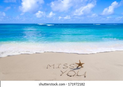 """Sign""""Miss you"""" with starfish on the sandy beach by the ocean"""