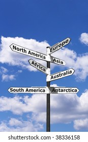Signpost with arrows pointing to the seven continents of the world against a blue cloudy sky.