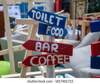 Signpost to bar, food, coffee and toilet. Festival, party or event. Part of a serie.