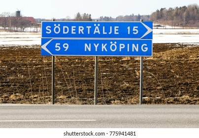 Signpost at the intersection with the distance in kilometers to Sodertalje and Nykoping.