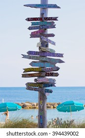 A signpost at a Key West, Florida, beach pointing towards places around the world and stating their distance in miles.