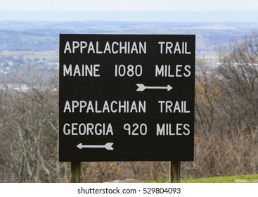 A signpost marking the distance to the beginning and end of the Appalachian Trail from Penn Mar, Washington County, Maryland, USA.  The sign is in Maryland, and Pennsylvania is in the background.