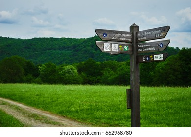 Signpost on crossing in front of a field and forest