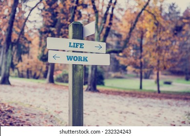 Signpost in a park or forested area with arrows pointing two opposite directions towards life and work, concept of conflict between family and career.