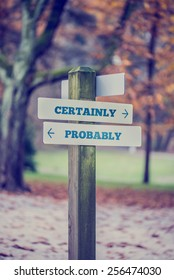 Signpost in a park or forested area with arrows pointing two opposite directions towards Certainly and Probably, retro effect faded look.