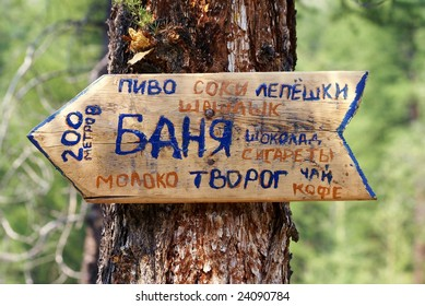 signpost to sauna and buffet in altai mountains russia - cyrillic alphabet