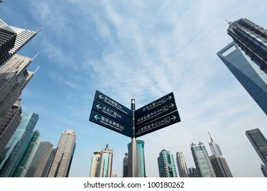 signpost with shanghai skyline of the lujiazui financial center at daytime