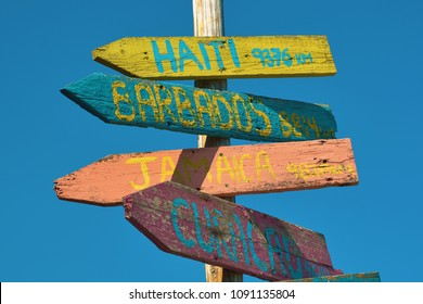 Signpost with signs for travelers with signs in the form of multi-colored wooden arrows with inscriptions and kilometers of distance at the seashore against the blue sea