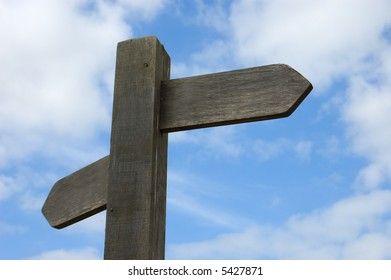 Signpost with two direction arrows. Left blank for your own text set against a blue sky