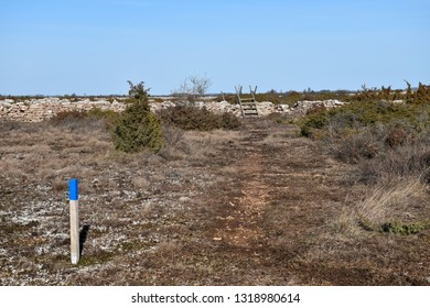 Signpost and a wooden stile by a footpath at the great plain alvar land on the swedish island Oland