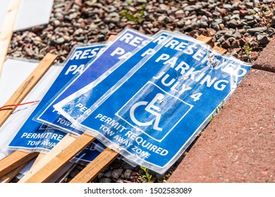 Signposts on ground for July 4th Independence day disabled parking spots with blue symbol and sign for reserved parking permit required tow away zone
