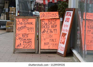 Signs outside butchers shop advertising produce with prices