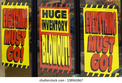 signs promote a giant sale as a store clears inventory before the location closes for business.