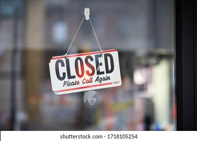 """Signs saying """"closed"""" on glass doors of shops and other small businesses"""