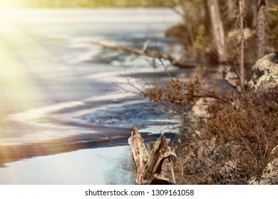 Signs of spring for Earth watchers, Earth observers. Snow on ice lakes saturated with water and blue. Forest lake in Lapland and sun's rays, Shore clearing form, submerged land-fast ice overnight