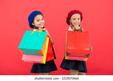 Signs you are addicted to shopping. Kids cute schoolgirls hold bunch shopping bags. Children pupils satisfied by shopping red background. Obsessed with shopping and clothing malls. Shopaholic concept.
