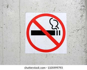 The sign-smoking is prohibited, pasted on a white uneven wall.