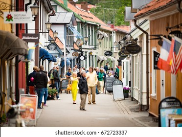 Sigtuna, Sweden - 23 July, 2013: old town street in City of Sigtuna, Sweden, Europe. Beautiful sunny day with tourists walking in street.