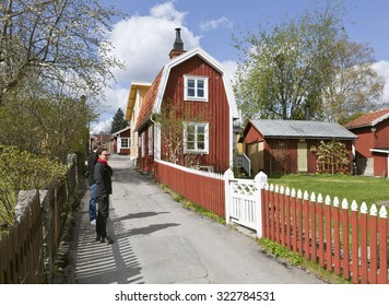 SIGTUNA, SWEDEN ON MAY 03. Street view of a small town in early spring on May 03, 2015 in Sigtuna, Sweden. Small wooden buildings, gardens and unidentified people.