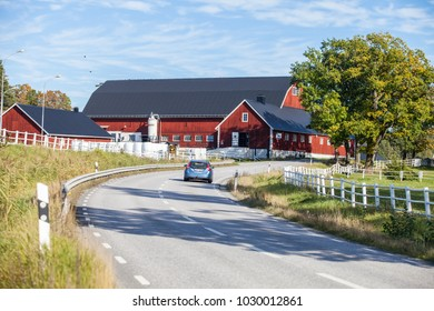 SIGTUNA, SWEDEN, SEPTEMBER 2015, a big, red painted, traditional farm on a sunny summer day with a road passing by.