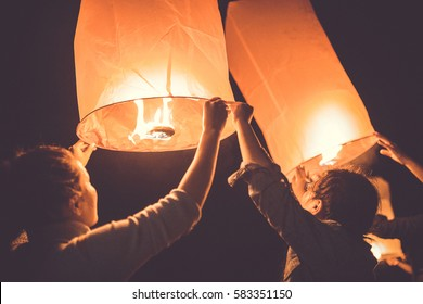 SIHANOUKVILLE, CAMBODIA - 31 DECEMBER, 2016: Undefined young people on the beach releasing floating paper lanterns in the sky during the New year celebration on OTRES BEACH in SIHANOUKVILLE, CAMBODIA.