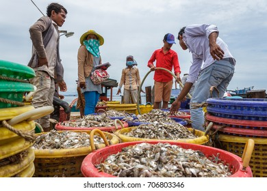 SIHANOUKVILLE, CAMBODIA - 7/20/2015: A group of workers help fishermen prepare on the docks of a fishing village.