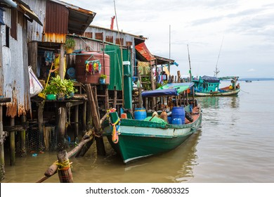 SIHANOUKVILLE, CAMBODIA - 7/20/2015: A local resident sweeps her home built on stilts in a fishing village.