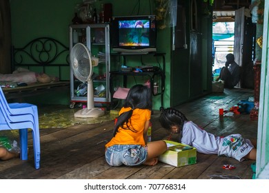 SIHANOUKVILLE, CAMBODIA - 7/20/2015: Two girls sit on the floor and color inside their house in a rural fishing village.