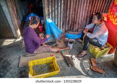 Sihanoukville, Cambodia. February 26,2019: Fisherman' s wife mending fishing net while chatting with friend at Sihanoukville Fishing Village.