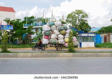 Sihanoukville / Cambodia - June 1 / 2019 : an excessively loaded trailer is carried by a scooter on a road