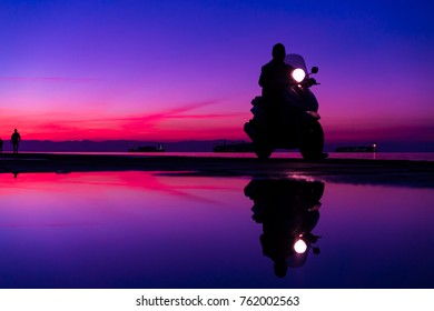 Sihouette of Man with a motorbike, riding by the Sea, against beautiful after sunset Blue and purple color tones