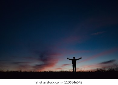 Sihouette of person opening arms to the sky at sunset or sunrise with orange clouds.