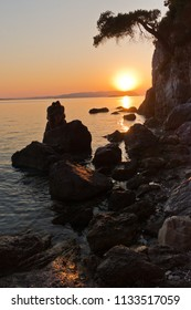 Sihouette of a young couple sitting on a rock at sunset, Kastani Mamma Mia beach, island of Skopelos, Greece