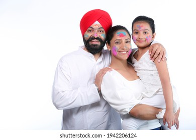 Sikh family celebrating holi and looking at camera