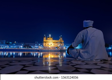 Sikh pilgrim in traditional clothes looking at evening Golden Temple. Holy Sikh Place Harmandir Sahib (gurdwara Golden Temple). Amritsar, Punjab, India