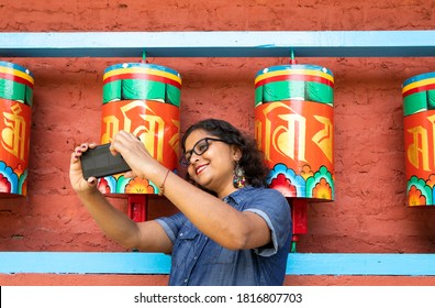 Sikkim, India, 12th Aug. 2019 : a beautiful lady in a blue dress taking selfie with a smart phone in front of buddhist prayer wheels in a monastery in Sikkim in India