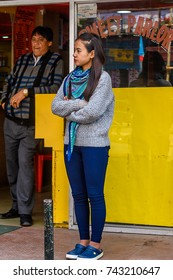 SIKKIM, INDIA - MAR 13, 2017: Unidentified Indian girl in grey pullover and blue pants stands with crossed hands.