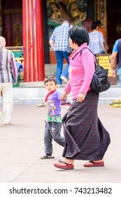 SIKKIM, INDIA - MAR 13, 2017: Unidentified Indian woman in long dress walks along the street.