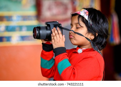 SIKKIM, INDIA - MAR 13, 2017: Unidentified Indian little girl in red shirt with hair hoop holds a camers in her hands.