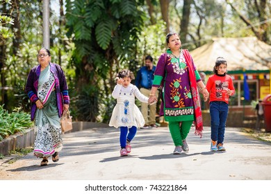 SIKKIM, INDIA - MAR 13, 2017: Unidentified Indian woman in traditional clothes walks with two little girls along the park.