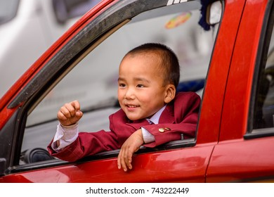 SIKKIM, INDIA - MAR 13, 2017: Unidentified Indian little boy looks out of the red car.