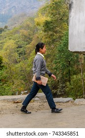 SIKKIM, INDIA - MAR 13, 2017: Unidentified Indian girl walks along the road with a notebook in her hand.