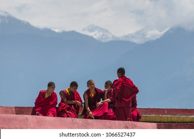 Sikkim, India - May 2, 2017: Tibetan monks rest at upper level of Rumtek Monastery near Gangtok with Himalayas mountains on background, Sikkim, India