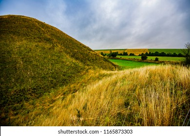 Silbury Hill, near Avebury, Wiltshire, England. It is the largest artificial neolithic mound in Europe, made around 2,400 BCE by a new wave of Beaker People. It covers 5 acres and is 40 metres high.