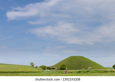 Silbury Hill is a prehistoric artificial chalk mound near Avebury in the English county of Wiltshire.  Its original purpose is still debated.